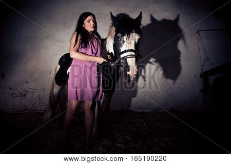 young woman standing next to her horse in the stables.