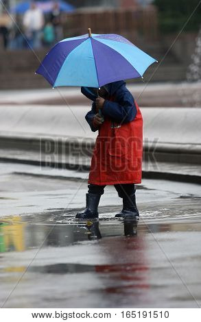 The boy in a raincoat and rubber boots goes under an umbrella in rainy day walking in puddles