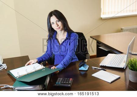 Young beautiful woman working with documents in the workplace in the office