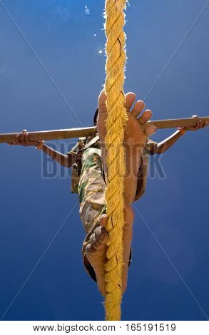 A girl balances herself with 4 metres pole as she walks along the rope.