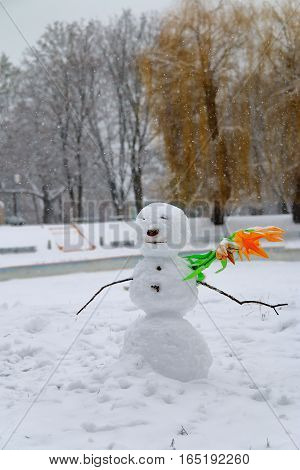 The picture was taken in the Ukraine. The picture shows a snowman. He stands alone in an empty park as an unknown stranger. Around it is snowing.