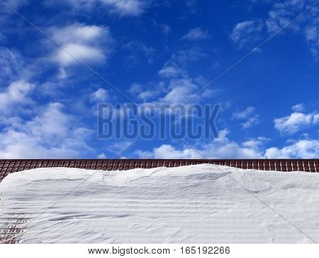 Roof In Snow And Blue Sky With Clouds