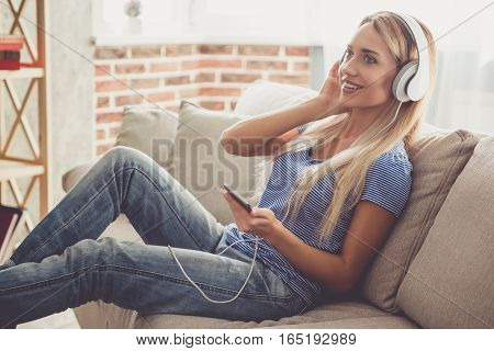 Beautiful girl in headphones is listening to music using a smartphone and smiling while sitting on couch at home