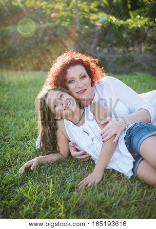 Happy family mother and daughter lie on the grass