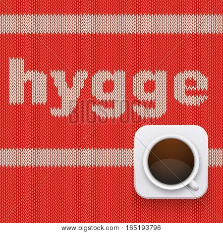 Word HYGGE on knitting texture with hot cup of coffee. Pleasure and comfort symbol. Vector Illustration isolated on white background.
