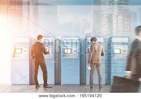Hallway of an office or a bank. A man is rushing by. Two businessmen are standing near ATM machines. There is a cityscape on the foreground. Toned image. Double exposure