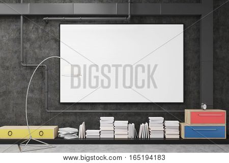 Close up of a large horizontal poster hanging on a black wall of a sitting room with colorful drawers a lamp and stacks of book