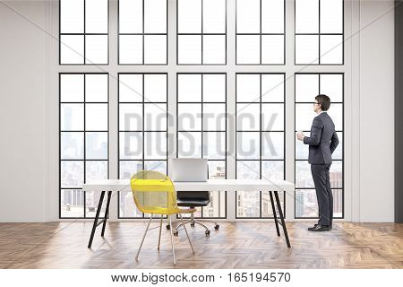CEO at his workplace with white desk an office chair and a transparent yellow visitor chair. Large windows are in the background. 3d rendering.