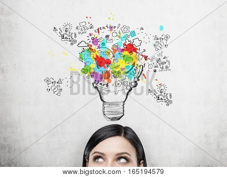 Close up of a woman's head. She is looking at a bright light bulb drawing on a concrete wall. Concept of a good idea