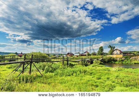 Suspension bridge across the river in the village. Village of Sloboda. Russia.Ural