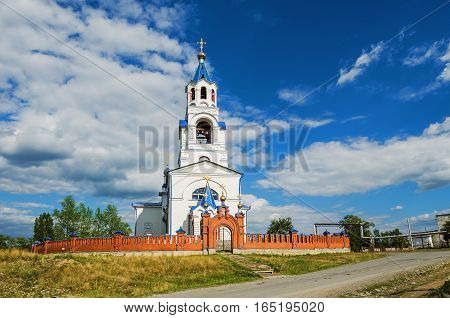 Church Of The Assumption Of The Blessed Virgin on the background of blue sky with clouds. Russia Ural village Novoutkinsk