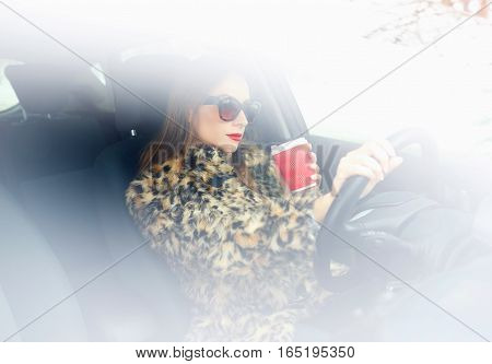 Beautiful woman in a fur coat with red lips with coffee to go driving her car