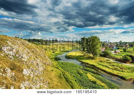 The view from the top of the cliff to the village of Novoutkinsk the river Chusovaya on a summer day. Russia The Urals