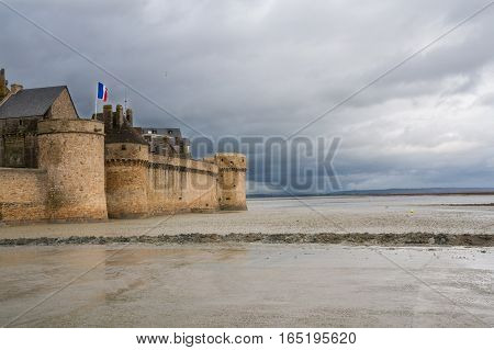 Le-Mont-Saint-Michel in France during low tide on a stormy day