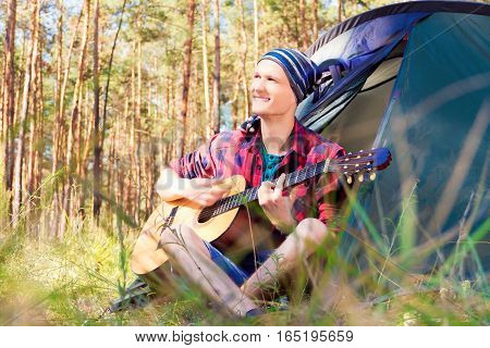 Guy sitting near the tent in the forest and playing guitar