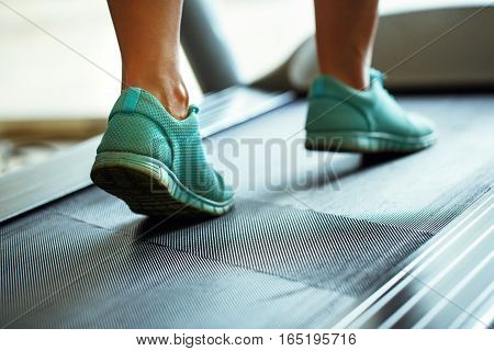 Foot of woman running on treadmill in gym