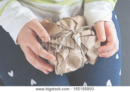 a Caucasian child girl unwraps kraft paper pulling a rope