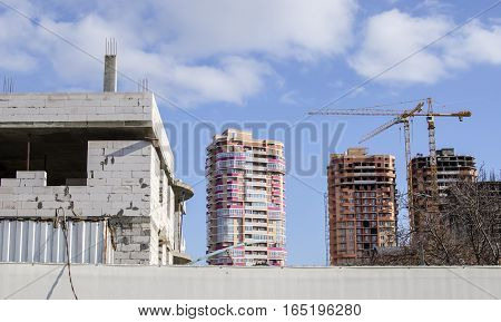Close-up of a white cottage under construction on the background of high-rise buildings