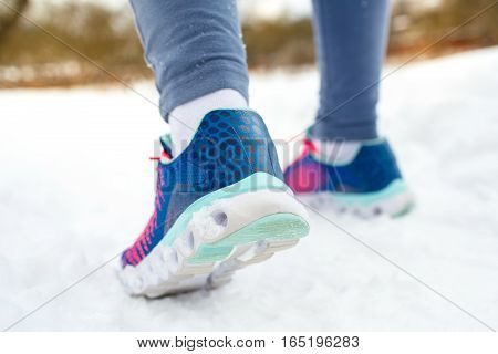 Running shoes - closeup of female sport fitness runner getting ready for jogging outdoors in winter