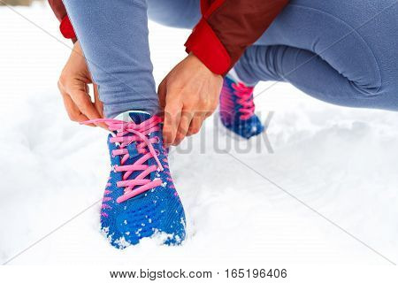 Running shoes - woman tying shoe laces. Closeup of female sport fitness runner getting ready for jogging outdoors on park in winter