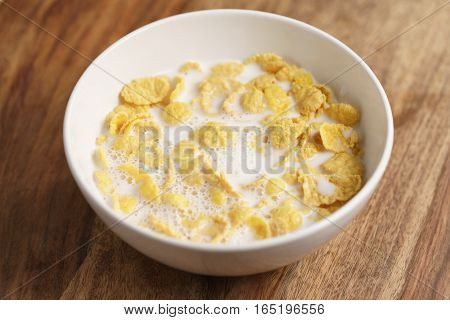 corn flakes with milk in white bowl on wood table, simple healthy breakfast