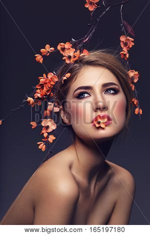 Beautiful young woman with make-up and loose hairdo. Artificial sakura branch with orange flowers hanging over head. Beauty shot on dark background. Copy space.