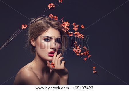 Beautiful young woman with make-up and loose hairdo holding artificial sakura branch with orange flowers. Beauty shot on dark background. Copy space.