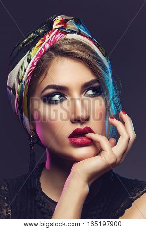 Beautiful young woman with bright makeup, red lips, colorful shawl on head and necklace. Studio beauty shot. Copy space.