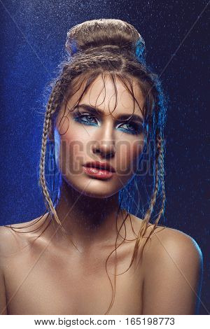 Beautiful blonde young woman with braids hairdo and blue bright makeup covered in water drops. Studio beauty shot. Copy space.