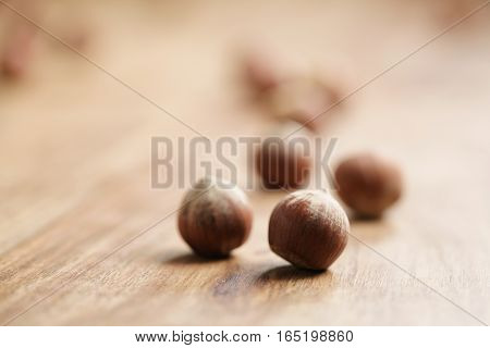 organic hazelnuts on old wooden table closeup photo, shallow focus