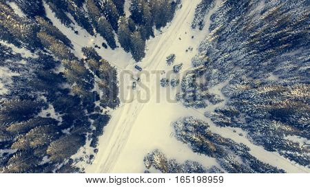 Aerial view of snow covered road through a forest. Pokljuka - Slovenia.