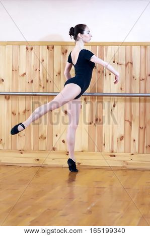 Beautiful young female classical ballet dancer on pointe shoes wearing black leotard a in class classical dance against wood wall and handrail. Ballet