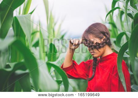 Young Women Braided Hair Wearing A Red Shirt Standing In A Cornfield. Hipster Concept.