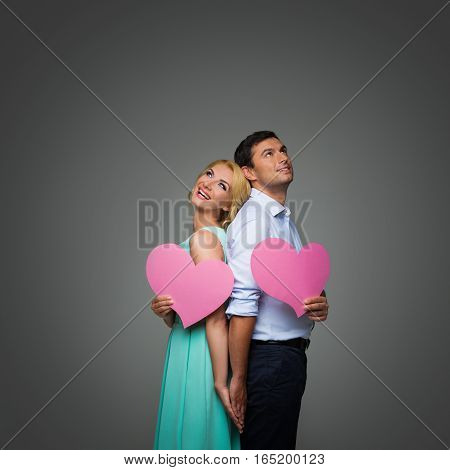 Beautiful young couple holding big pink hearts looking up. Blond woman in mint dress and handsome man in shirt and trousers standing on grey background. Valentine's day concept. People in love. Copy space.
