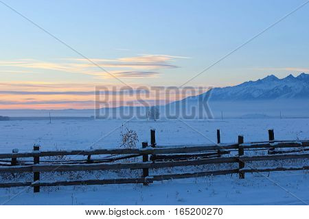 Wooden fence, snow field and mountains in the winter