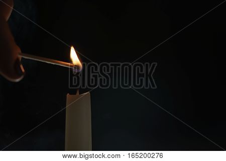 tall candle lighting in the dark environment, shallow focus