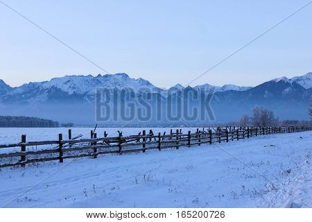 Snowy field, mountain slopes, and wooden fence