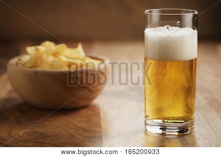 glass of lager beer with potato chips on wooden table, focus on beer