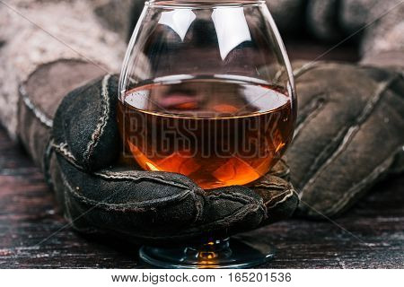 Human hands in winter sheep skin gloves holding glass of brandy. Front closeup view