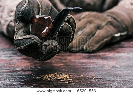 Human hands in winter gloves holding smoking pipe. Front view