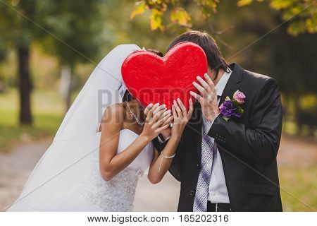 Happy wedding couple holds big red heart in hands. the groom and the bride hold big red heart in hand. newly married during a kiss have hidden the faces in red heart. St. Valentine's Day.