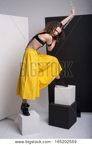 Fashion Photo Of Beautiful Girl Posing In Studio. Wearing Yellow Shorts, Black Boots. Straps Over Br