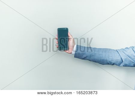 New shiny phone in male hands on a gray background