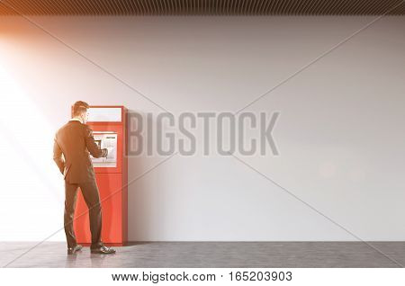 Rear view of a tall businessman withdrawing cash from a red ATM machine. Concept of financial operations. Mock up. Toned image