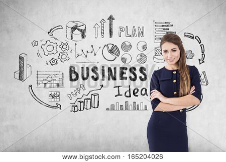 Smiling brown haired woman with crossed arms is wearing a dress and standing near a concrete wall with business idea icons