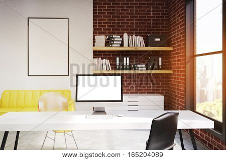 Front view of a computer monitor standing on a white office desk. There is a yellow sofa bookshelves and a framed poster. 3d rendering. Mock up. Toned image