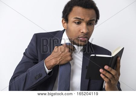 Close up of an African American man reading a small black notebook and taking off his tie. Concept of getting ready for a board meeting.