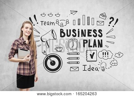 Portrait of a smiling blond woman in a checkered shirt standing with her tablet near a concrete wall with business plan icons. Concept of business education