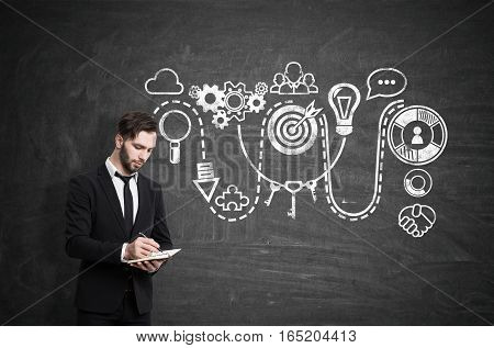 Portrait of a thoughtful businessman in a black suit with a notebook standing near a blackboard with a creative start up drawing on it.