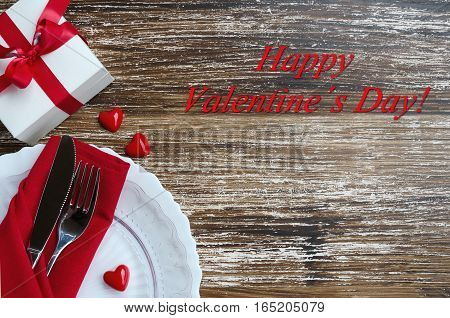 Elegant table setting in white red tone for celebrate St Valentines Day. Top view of plate cutlery line napkin gift box with bow and decorative valentine heart on wooden background with copy space. Love romantic dinner concept.